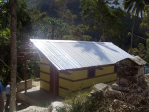 Haitians earn traditional housing (ti-kay, little house), built primarily by Building Goodness Foundation, as a member of CODEP
